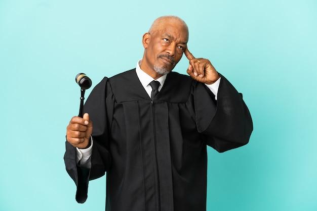 Giudice uomo anziano isolato su sfondo blu che ha dubbi e pensa