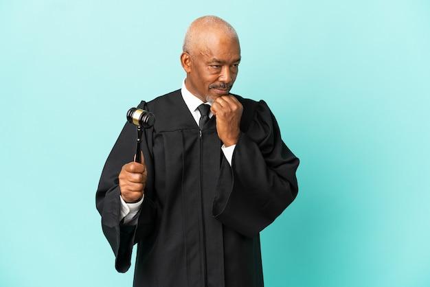Giudice uomo anziano isolato su sfondo blu avendo dubbi