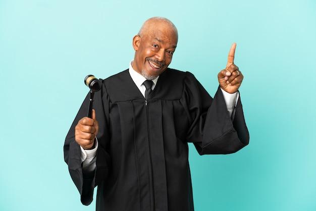 Giudice uomo anziano isolato su sfondo blu con l'intenzione di realizzare la soluzione sollevando un dito