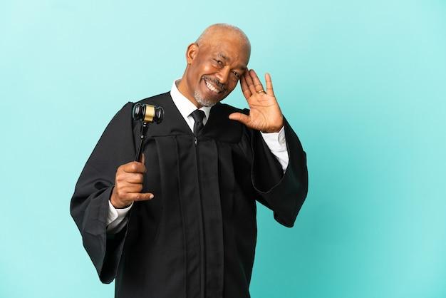 Giudice uomo anziano isolato su sfondo blu ascoltando qualcosa mettendo la mano sull'orecchio