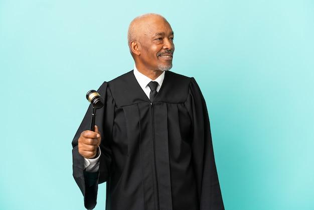 Giudice uomo anziano isolato su sfondo blu guardando lato