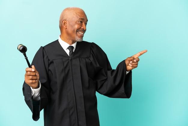 Giudice uomo anziano isolato su sfondo blu che punta il dito di lato e presenta un prodotto