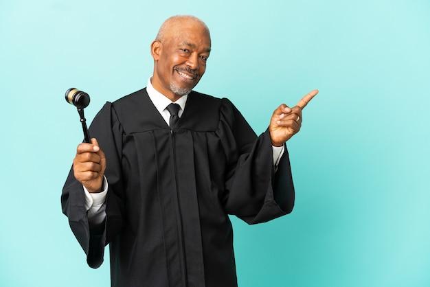 Giudice uomo anziano isolato su sfondo blu che punta il dito a lato