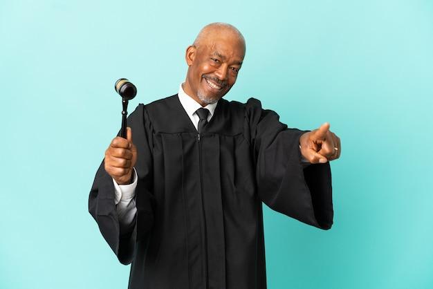 Giudice uomo anziano isolato su sfondo blu che punta davanti con espressione felice