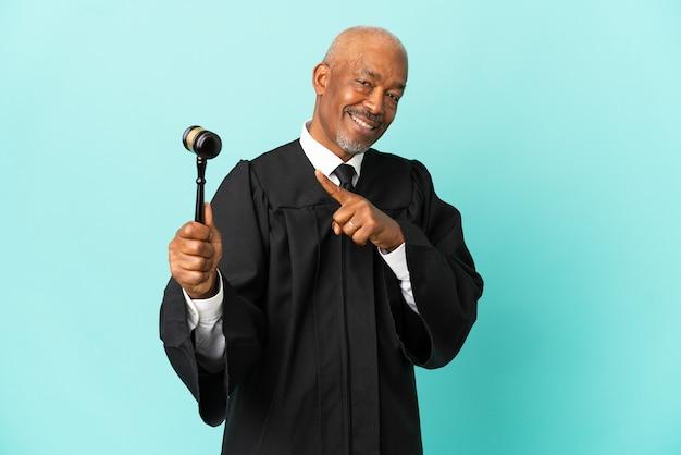 Giudice uomo anziano isolato su sfondo blu che punta al lato per presentare un prodotto