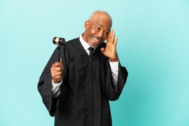 Giudice uomo anziano isolato su sfondo blu che grida con la bocca spalancata di lato