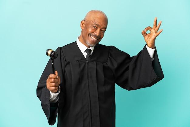 Giudice uomo anziano isolato su sfondo blu che mostra segno ok con le dita