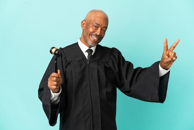 Giudice uomo anziano isolato su sfondo blu sorridente e mostrando segno di vittoria
