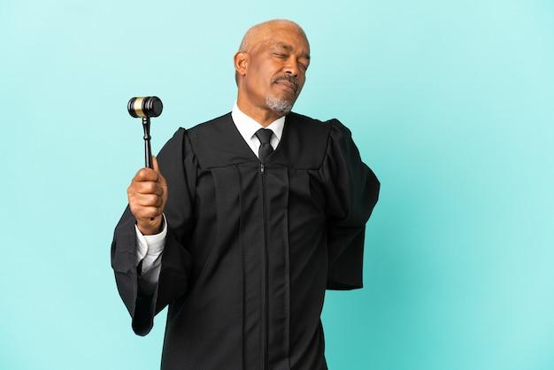Giudice uomo anziano isolato su sfondo blu che soffre di mal di schiena per aver fatto uno sforzo