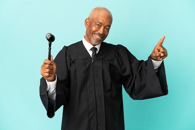 Giudice uomo anziano isolato su sfondo blu sorpreso e puntando davanti