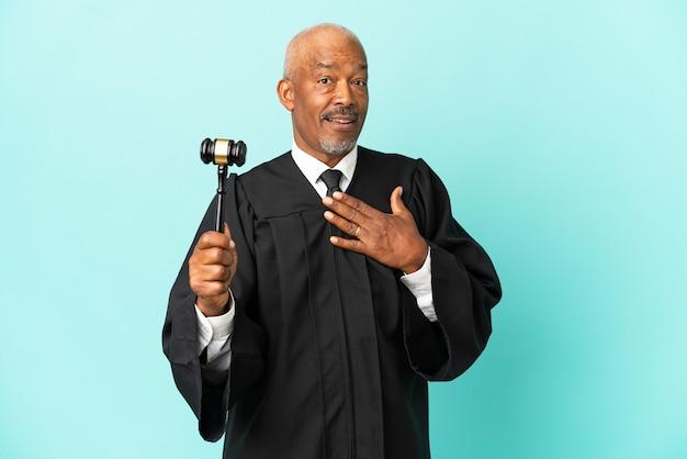 Giudice uomo anziano isolato su sfondo blu sorpreso e scioccato mentre guarda a destra