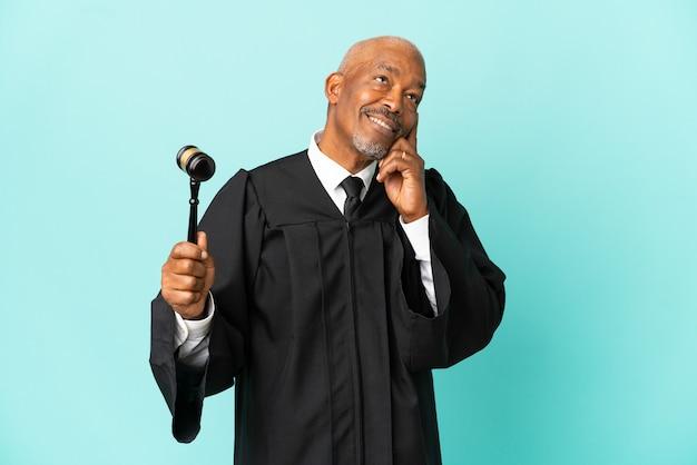 Giudice uomo anziano isolato su sfondo blu pensando a un'idea mentre guarda in alto looking