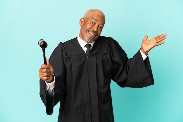 Giudice uomo anziano isolato su sfondo blu con espressione facciale scioccata