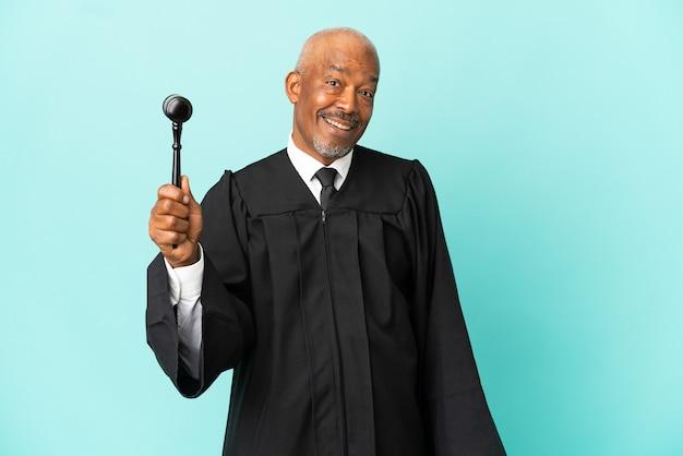 Giudice uomo anziano isolato su sfondo blu con espressione facciale a sorpresa