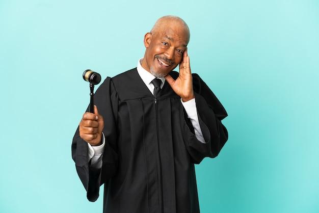 Giudice uomo anziano isolato su sfondo blu con espressione facciale sorpresa e scioccata
