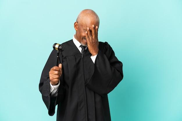 Giudice uomo anziano isolato su sfondo blu con espressione stanca e malata