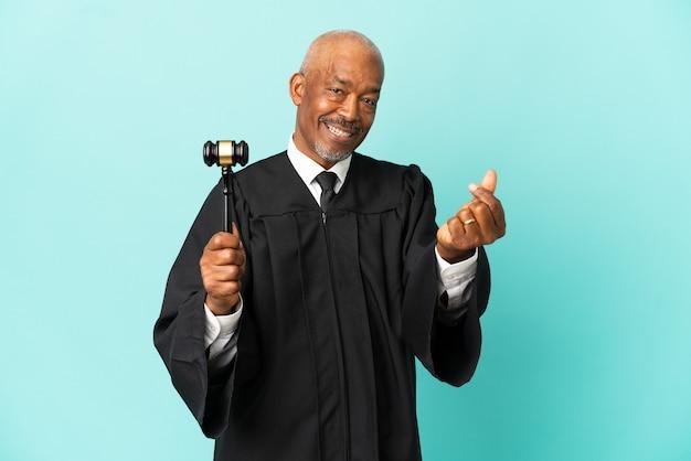 Giudice l'uomo anziano isolato sulla superficie blu che fa il gesto dei soldi