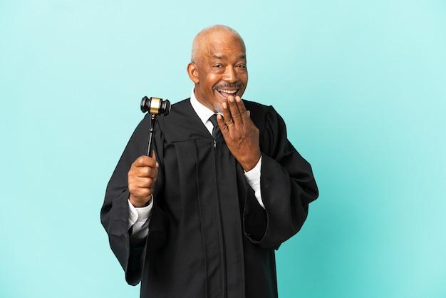 Giudice uomo anziano isolato sulla parete blu felice e sorridente che copre la bocca con la mano