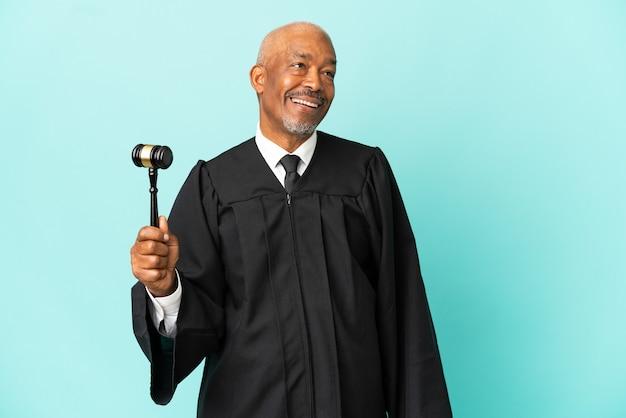 Giudice uomo anziano isolato sul muro blu che ride