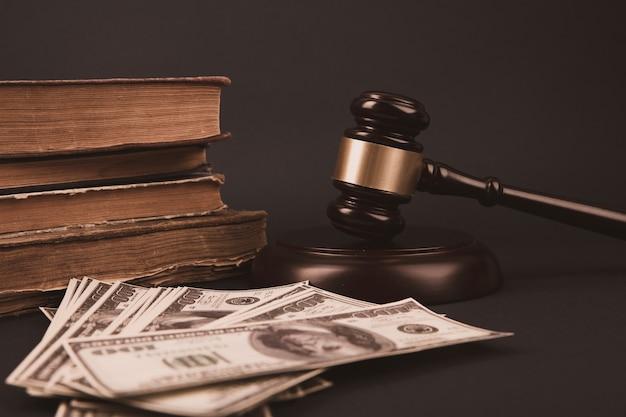 Martelletto di legno del giudice con il concetto della banconota dei soldi del dollaro per la corruzione