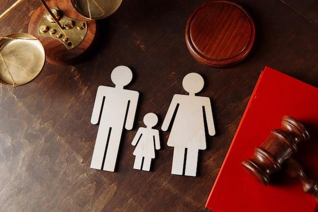 Martelletto dei giudici su un libro rosso e figure di famiglia