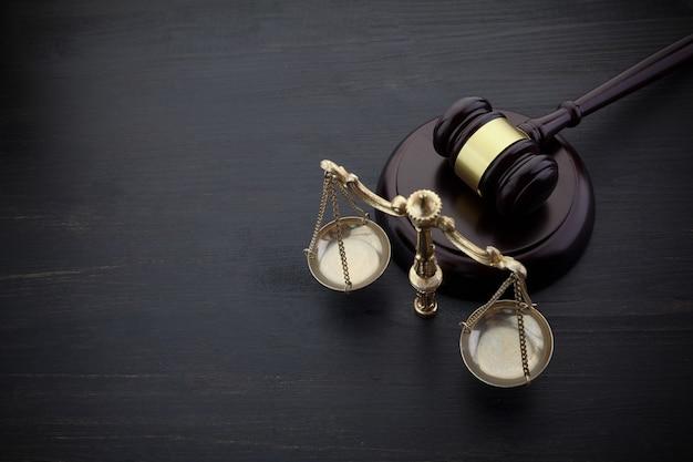 Martelletto dei giudici e scala di giustizia sul tavolo nero
