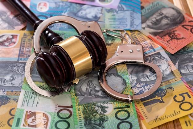 Martelletto dei giudici con le manette sui dollari australiani
