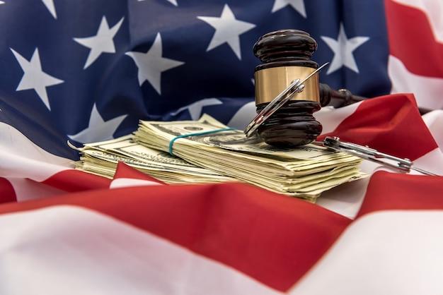 Martelletto dei giudici con manette e banconote da un dollaro sopra la bandiera dell'america