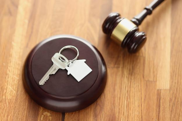 Martelletto di legno dei giudici e chiavi di casa sdraiato sul tavolo. vendita di immobili al concetto di asta