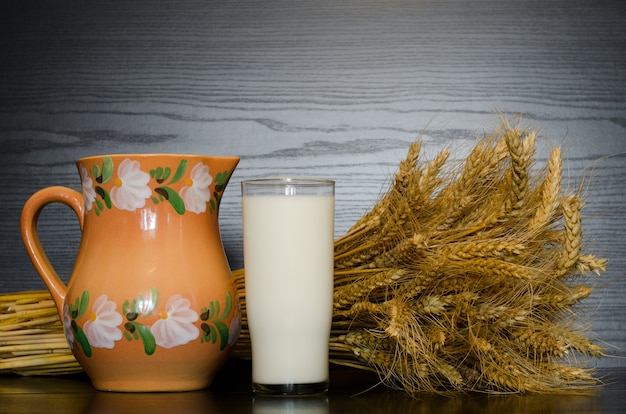 Brocca, bicchiere di latte e un covone Foto Premium