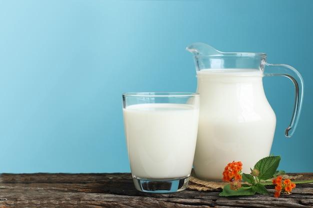 Una brocca di latte e un bicchiere di latte su un tavolo di legno su sfondo blu.