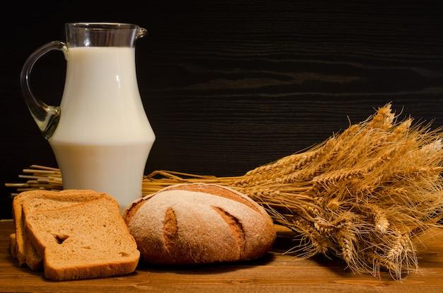 Brocca di latte, pane di segale rotondo e quadrato, un covone sul tavolo di legno, sfondo nero, spazio per il testo