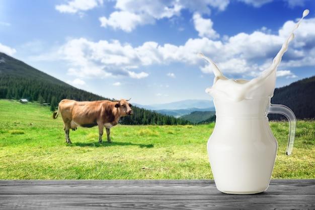 Brocca di latte con splash con mucca marrone in montagna