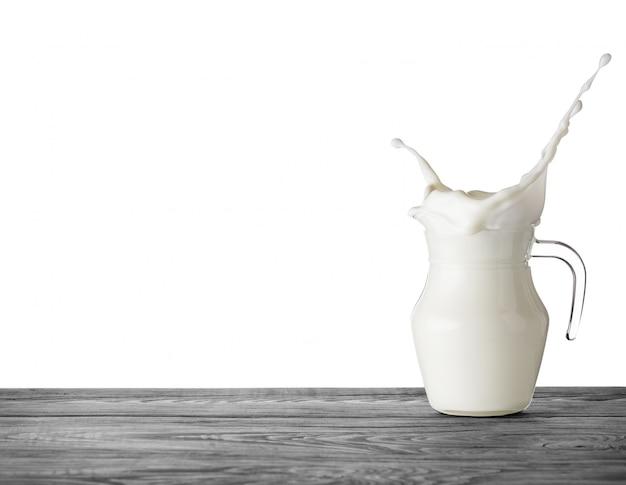 Brocca di latte con spruzzata sulla tavola di legno