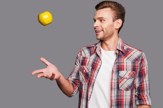 Destreggiarsi tra il suo stile di vita sano. un uomo sorridente che lancia una mela in aria mentre sta in piedi su uno sfondo grigio