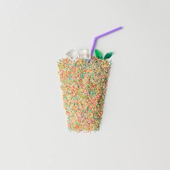 Bicchiere di succo fatto di torta colorata spruzza con cubetti di ghiaccio.
