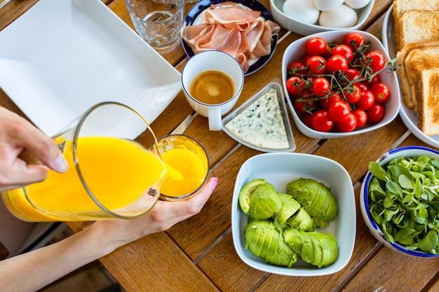 Il succo viene versato in un bicchiere succo d'arancia per colazione tavolo con cibo per colazione arancia
