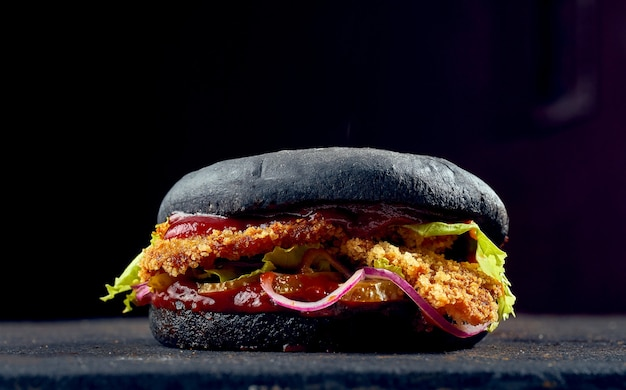 Hamburger succoso con panini neri con bocconcini di pollo, formaggio, cetriolo e salsa di pomodoro su sfondo scuro.