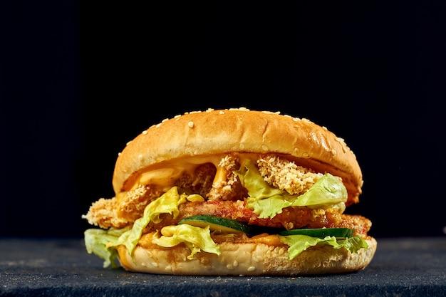 Hamburger succoso con bocconcini di pollo, formaggio, cetriolo e pomodoro, salsa su sfondo scuro.