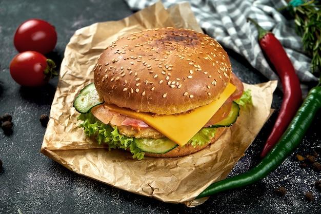 Hamburger succoso con pollo, pomodori, formaggio e cipolle croccanti su un tavolo scuro. hamburger di pollo