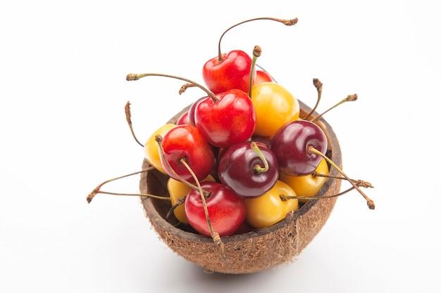 Bacca succosa della ciliegia in una ciotola di cocco su un bianco