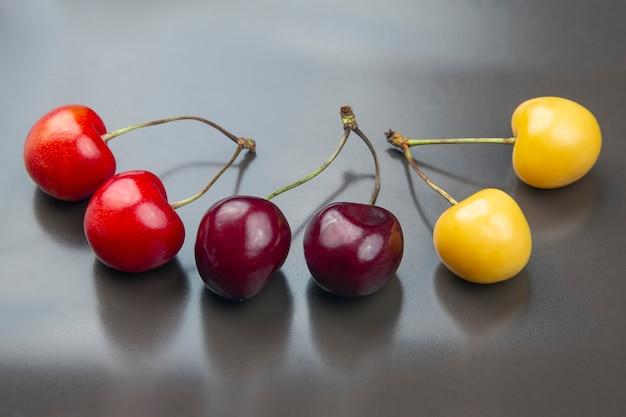 Bacca succosa della ciliegia su un tavolo grigio.