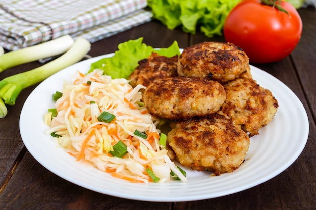 Cotolette succose e insalata con verdure fresche: cavolo, carote, verdure su un piatto bianco.