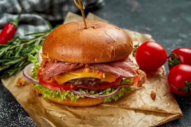 Doppio hamburger succoso con carne di manzo, pomodori pancetta, formaggio e cipolle croccanti su un tavolo scuro.