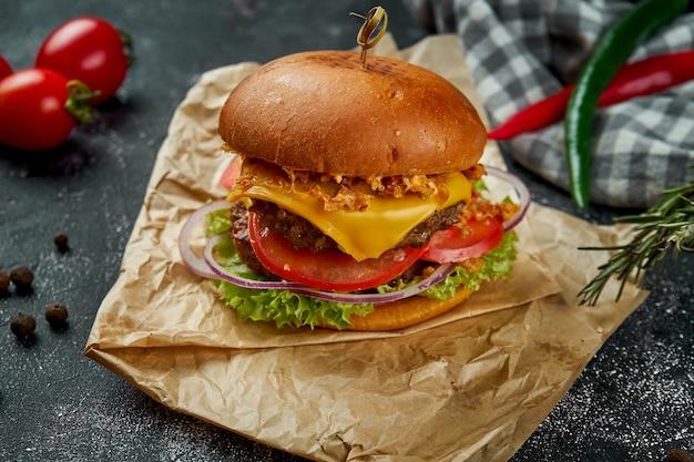 Doppio hamburger succoso con carne di manzo, pomodori, formaggio e cipolle croccanti su un tavolo scuro.
