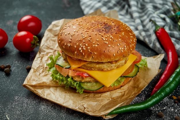 Doppio hamburger succoso con pollo, pomodori, formaggio e cipolle croccanti su un tavolo scuro. hamburger di pollo