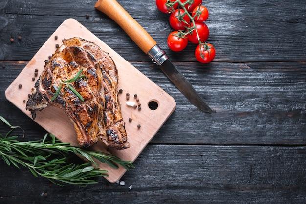 La succosa bistecca profumata giace su un tagliere, deliziose spezie sul tavolo, erbe aromatiche rosmarino e toam rosso.
