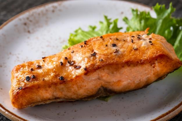 Filetto di salmone alla griglia succoso su un piatto. avvicinamento
