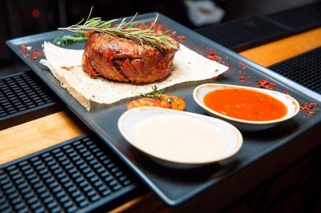 Una succosa bistecca alla griglia con due salse si siede su un piatto nero