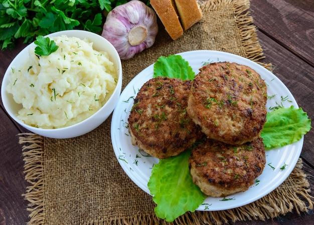 Homecutlets succosi (manzo, maiale, pollo) e purè di patate su uno sfondo di legno.